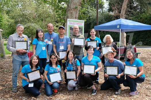 East Meets West board members Flora Wang (front row, from left), Queenie Ng, Sandra Chen, June Song, and Ron and Helen Gunnoe. Back: Isaac Hung, Annie and Paul Brassard, Matt and Julie Scott, and Molly Woodford.